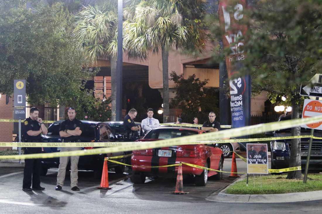 Poliser går igenom eventuella bevis och en sportbil vid McDonald's i Ybor City, Tampa.