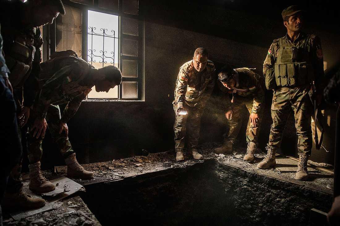 Kurdiska soldater kollar ner i en tunnel som hittades i ett av husen.