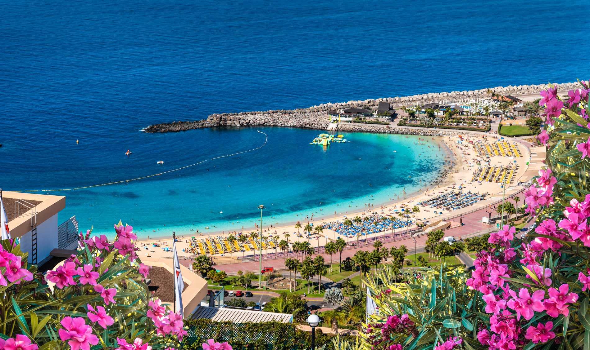 Playa de los Amadores är en vacker strand skyddad av en pir.