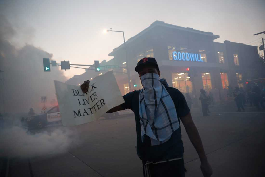 """En demonstrant i Minneapolis tvillingstad Saint Paul håller upp en skylt med texten """"Black Lives Matter"""" vilket kan översättas med """"Svarta liv har betydelse""""."""