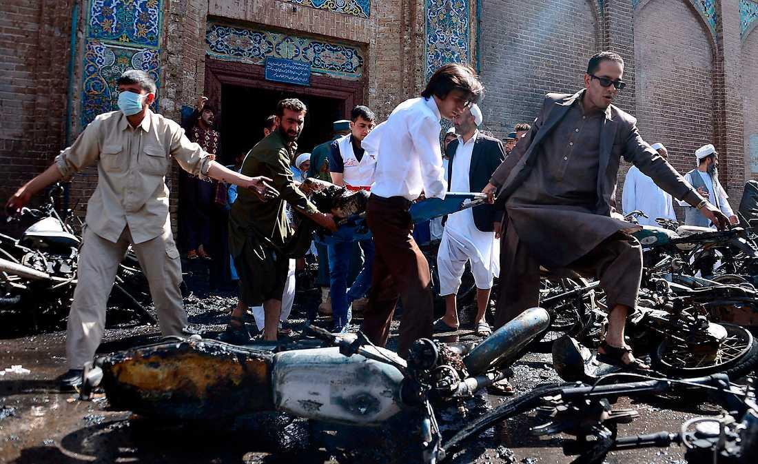 HÄR DOG SJU Frivilliga bär bort ett av offren sedan en motorcykelbomb briserat utanför en moské i Herat, Afghanistans tredje största stad, i tisdags. Sju människor dödades och 16 skadades.