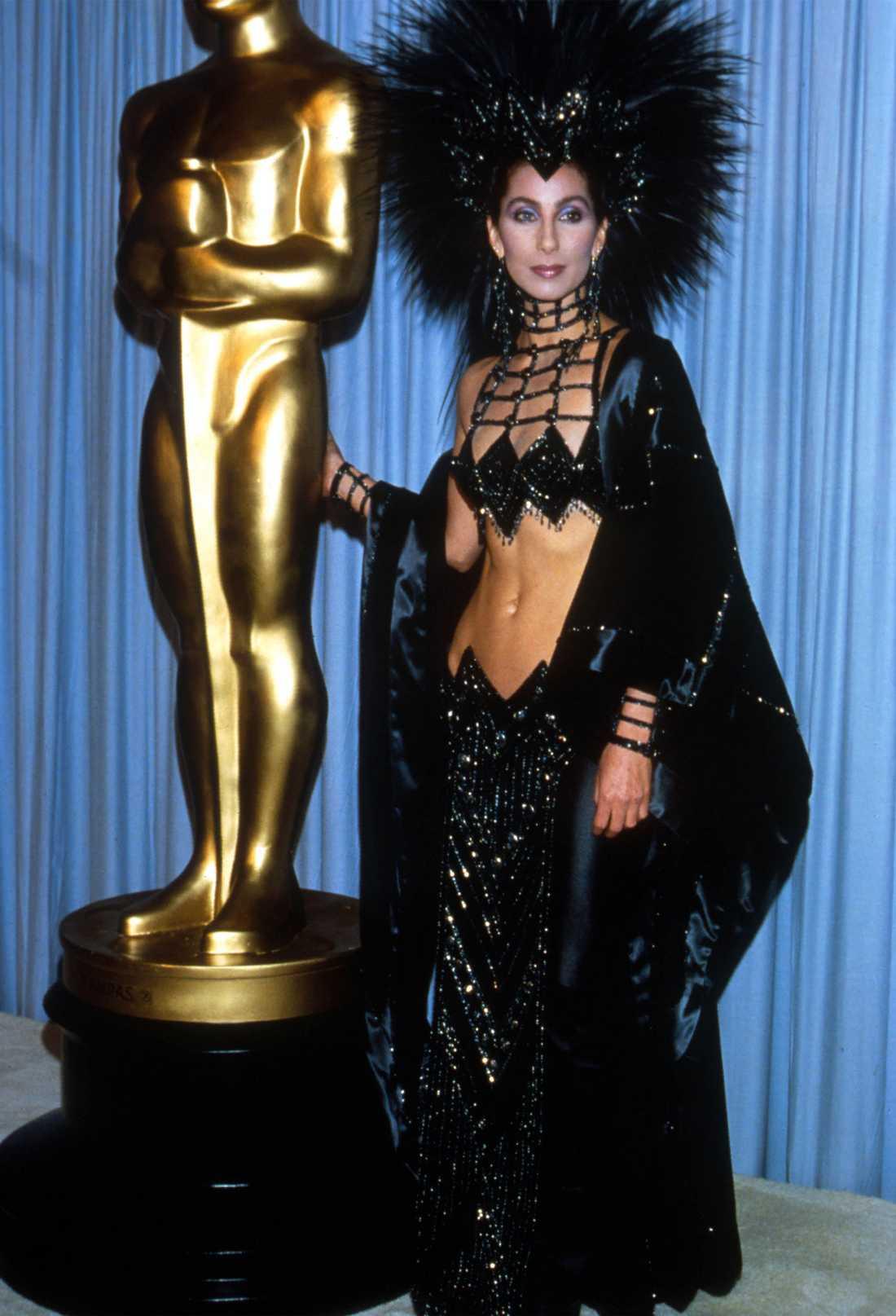 """Cher 1986… """"If you got it, flaunt it. Ja, så tänkte nog Cher när hon drog på sig den här klassiska Oscar-looken designad Bob Mackie. Enligt rykten fick hon sitta på golvet i taxin mot galan för att ha möjlighet att få plats med den där enorma fjäderperuken."""""""