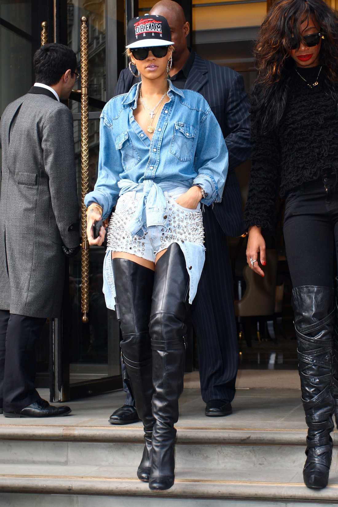 Rihanna har hakat på trenden med keps och till den väljer hon lårhöga skinnstövlar, nitshorts och jeansskjorta.