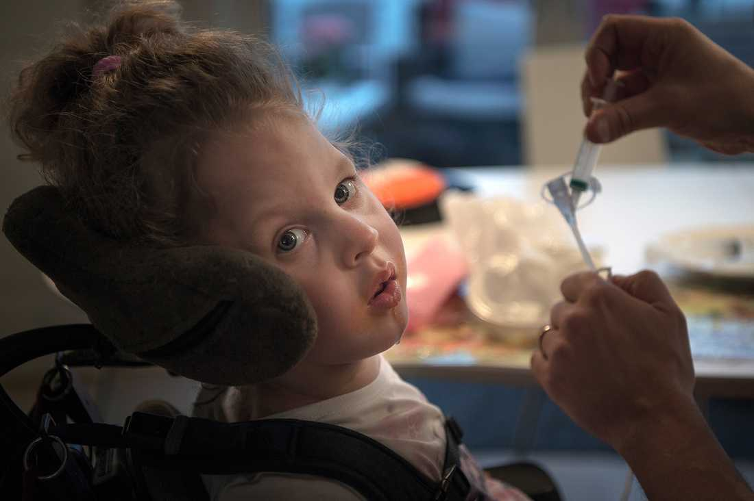 Elvira, 2,5, kan varken hålla uppe kroppen eller huvudet utan har en rullstol med nackstöd. Hon behöver mycket mediciner som hon ges genom sond via knapp i magen.