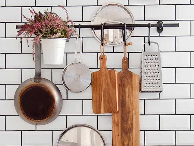 Även om stekpannor och skärbrädor skulle få plats i det välplanerade köket bidrar förvaringen på den kaklade väggen till rummets atmosfär.