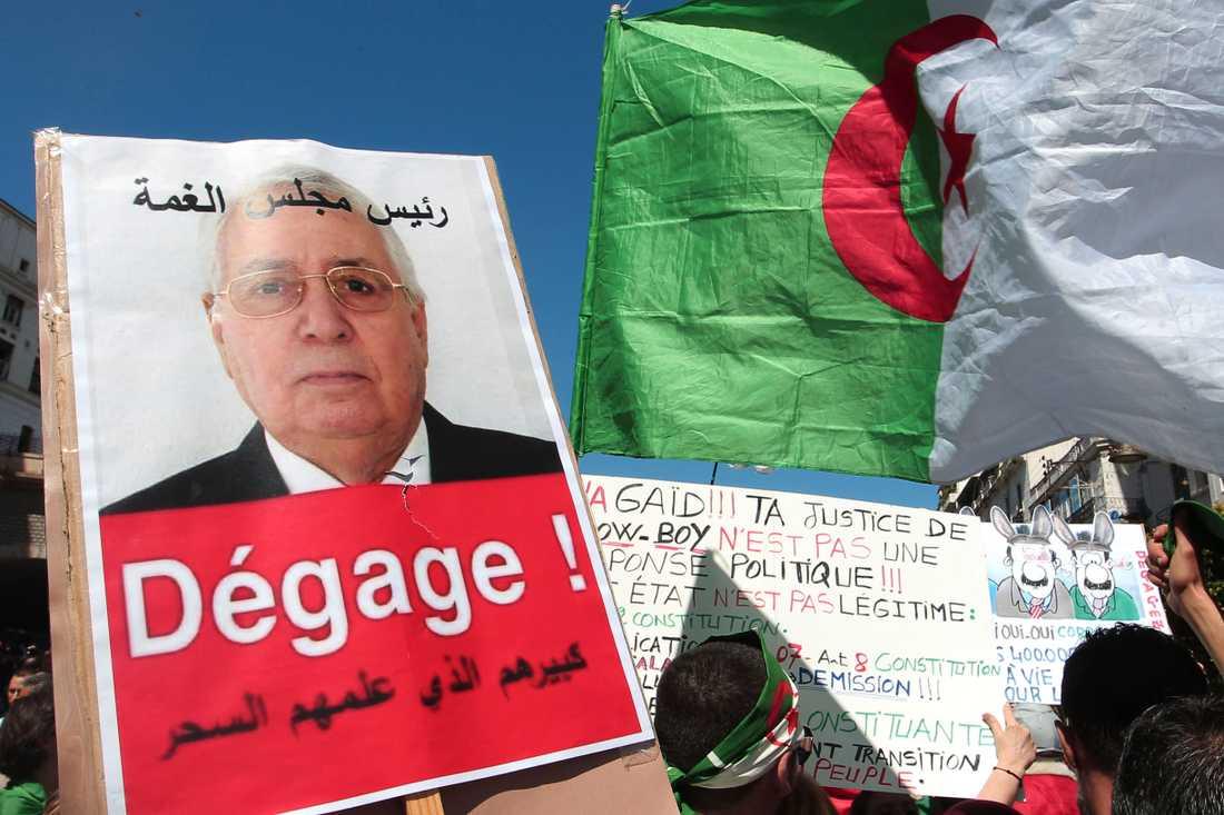 Ett plakat med interimspresidenten Abdelkader Bensalahs porträtt på, och uppmaningen att han ska avgå, under en av de många demonstrationerna mot makteliten i Algeriet. Arkivbild.
