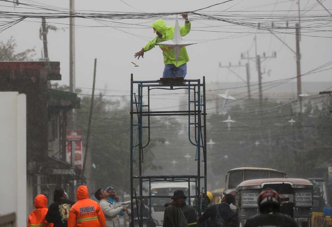 En man tar ned julbelysningen i provinsen Cavite söder om Manila inför orkanen Kammuri.