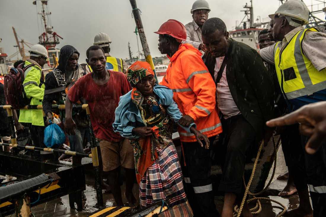 Folk från staden Buzi får hjälp efter att de anlänt med båt till Beira i Moçambique.