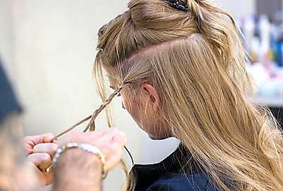 2 För allt hår till ena sidan. Gör en fläta av en del av underhåret på valfritt ställe. Spreja flätan med hårsprej så att den fixeras.