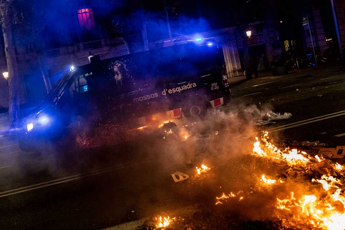 En polisbil kör över brinnande barrikader i Barcelona under natten till fredagen.
