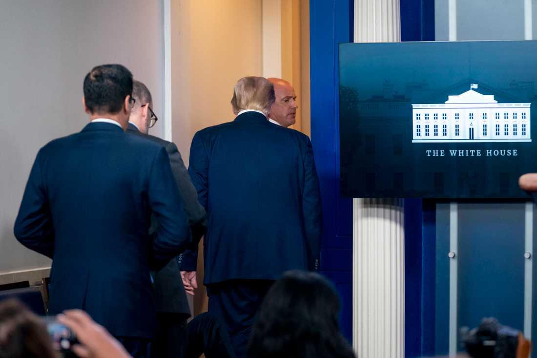 President Donald Trump lämnar presskonferensen tillsammans med personal från Secret Service.