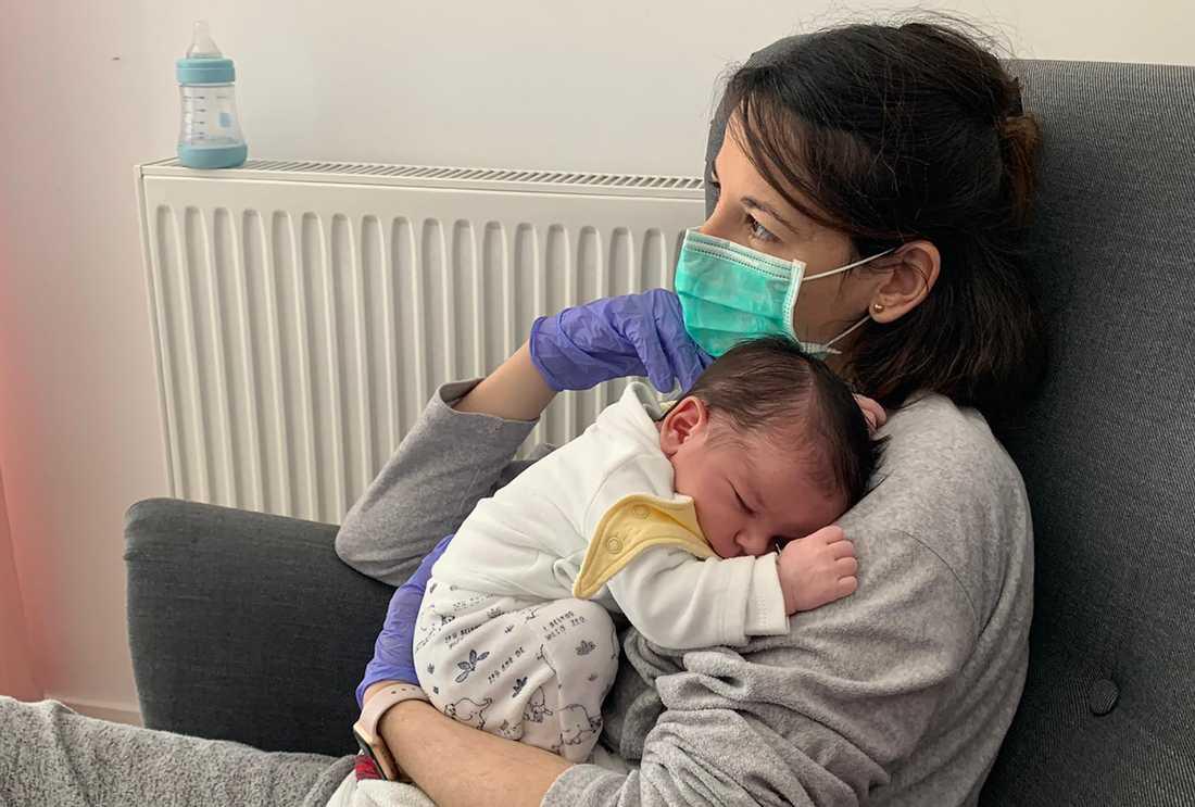 Vanesa Muro i Madrid håller sin nyfödde son Oliver. Än har hon, eller barnets pappa Oscar Carrillo, inte kunnat röra vid sonen utan plasthandskar av rädsla för att smitta honom med coronaviruset.