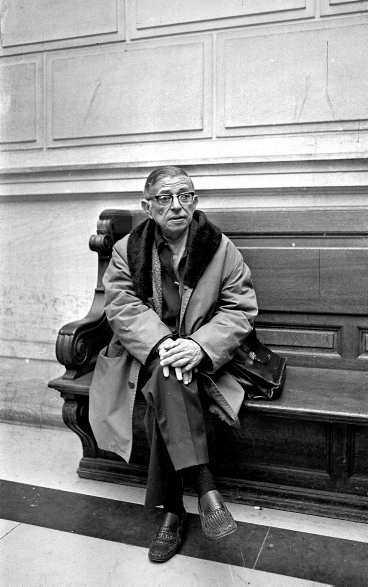 """I morgon fyller Jean-Paul Sartre hundra år, här fotograferad av Viollet inne på Palais de Justice. Vi uppmärksammar Sartre, """"denna filosofiska bödel"""", som Norman Mailer skriver i sin artikel. Anders Paulrud har varit på Bibliotheque National i Paris och sett en storslagen utställning om """"statsmannen"""" Sartre."""