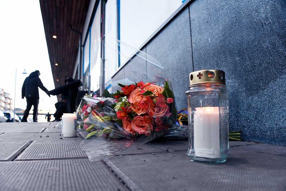 Utanför mordplatsen har blommor lagts ner och ljus tänts. På lördagskvällen uppges en grupp killar ha slängt blommorna.