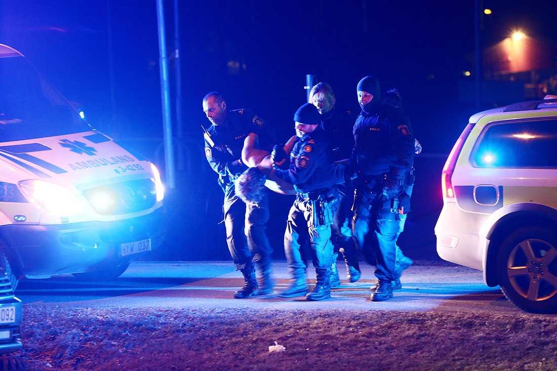 Polis bär iväg mannen som misstänks ha tänt på.