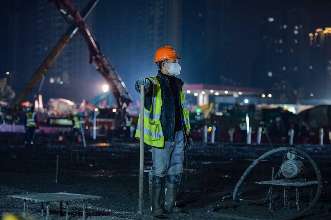 En byggnadsarbetare tar en kort rast vid bygget av ett av sjukhusen i Wuhan.