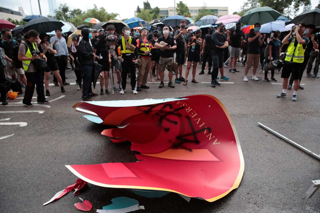 En skylt som informerade om Folkrepubliken Kinas 70-årsdag slets ned till jubel från demonstranter.