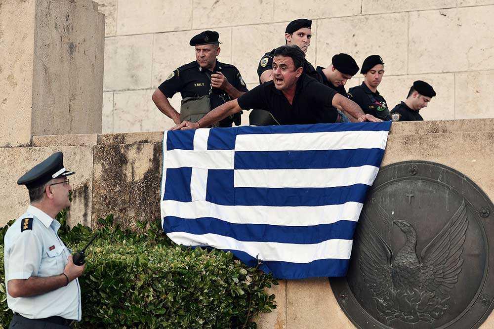 En demonstrant diskuterar med polisen utanför det grekiska parlamentet i Aten.