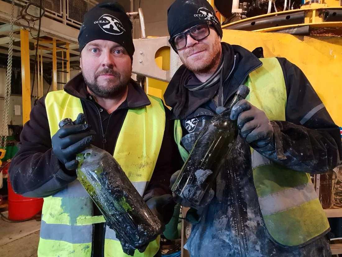 Dykaren Peter Lindberg (tv) och Floris Marsielle, specialist på undervattensteknik, med ett par av de 900 flaskor konjak och likör som nyligen bärgats från ett vrak i Ålands hav.