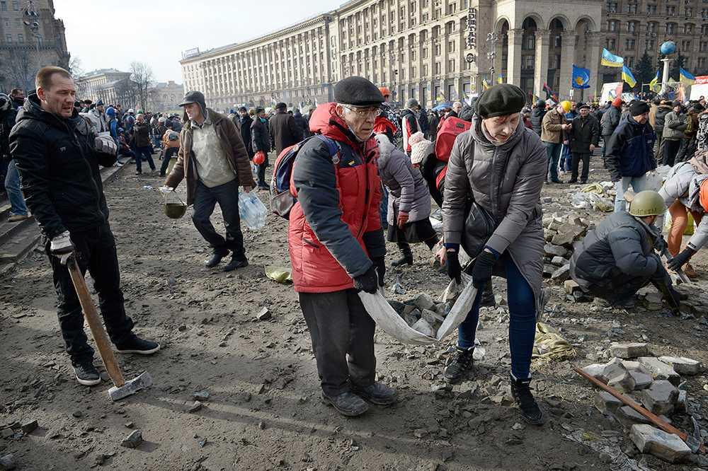 Ett äldre par bar fram stenar åt frontlinjen på barrikaderna.