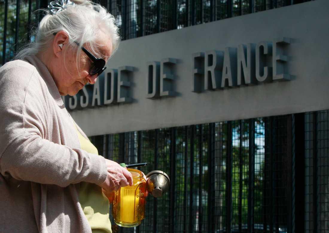 En kvinna i Polens huvudstad Warsawa tänder ett ljus efter attacken i Nice.