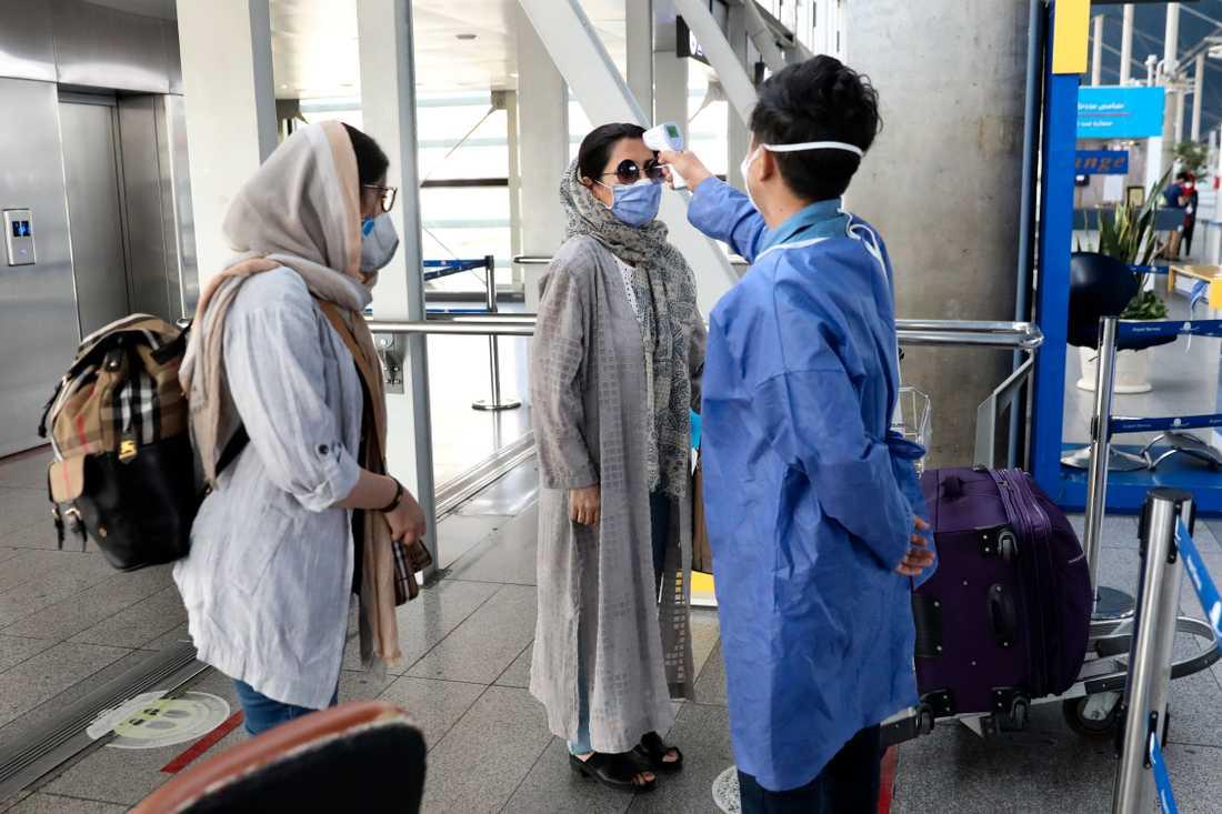 Vårdpersonal kontrollerar temperaturen på passagerare som anländer till Teheran. Arkivbild.