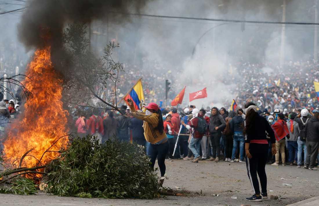Demonstranter bränner en barrikad i Ecuadors huvudstad Quito.