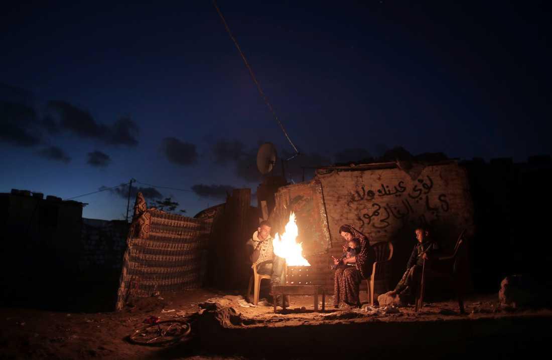 En familj värmer sig vid en öppen eld under ett strömavbrott i södra Gaza. Arkivbild.