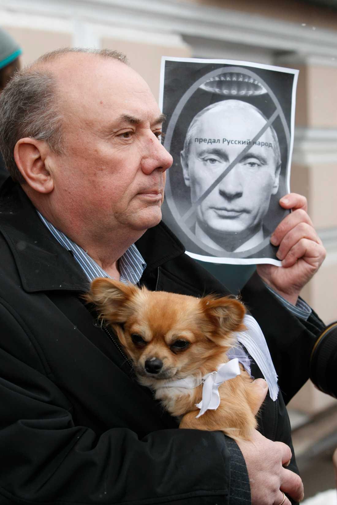 """Förråder ryska folket Mannen håller upp ett porträtt av Vladimir Putin med orden """"Förråder det ryska folket."""""""