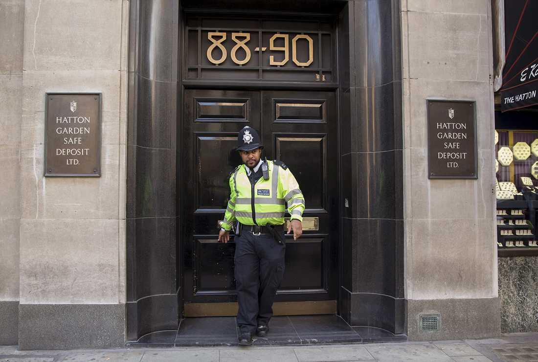En polis kommer ut från Hatton Garden, där runt 70 bankfack plundrats under påskhelgen.