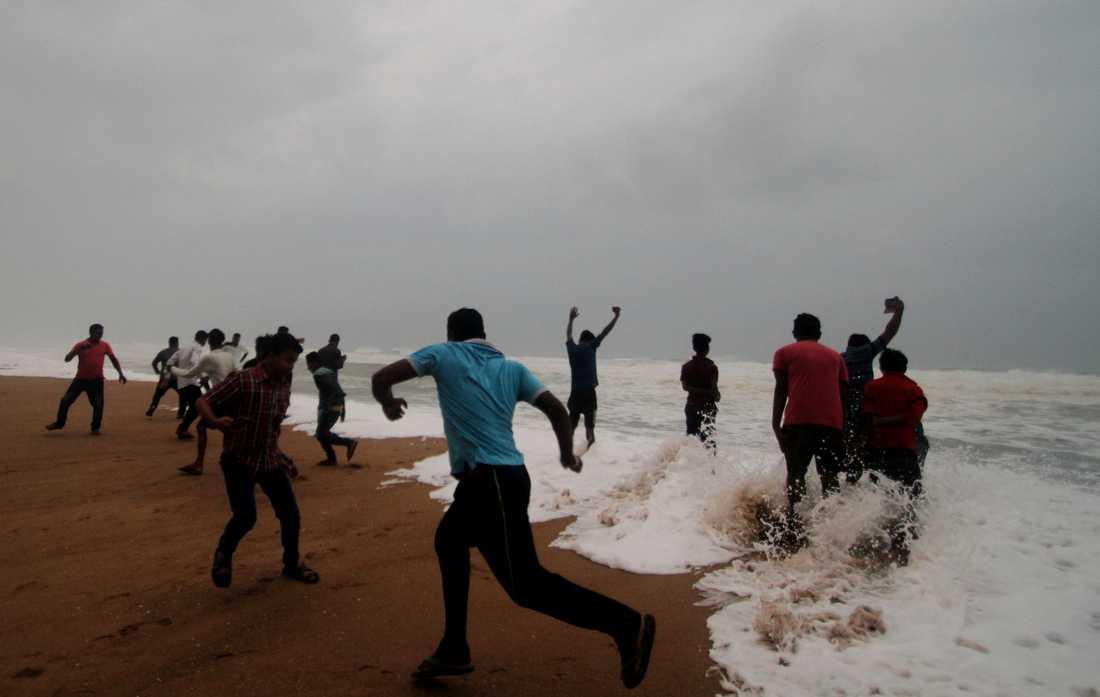 Människor i vågor på en strand i Odisha.