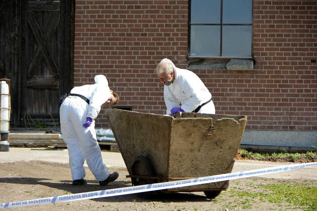 Polisens tekniker undersöker noggrant en kärra vid ladan i närheten av kaféet.