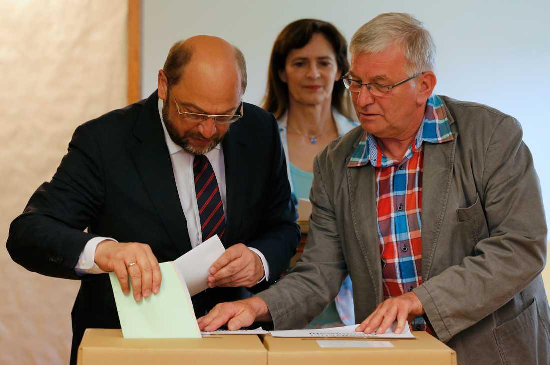 SPD:s Martin Schulz får hjälp av en valförrättare att avlägga sin röst.