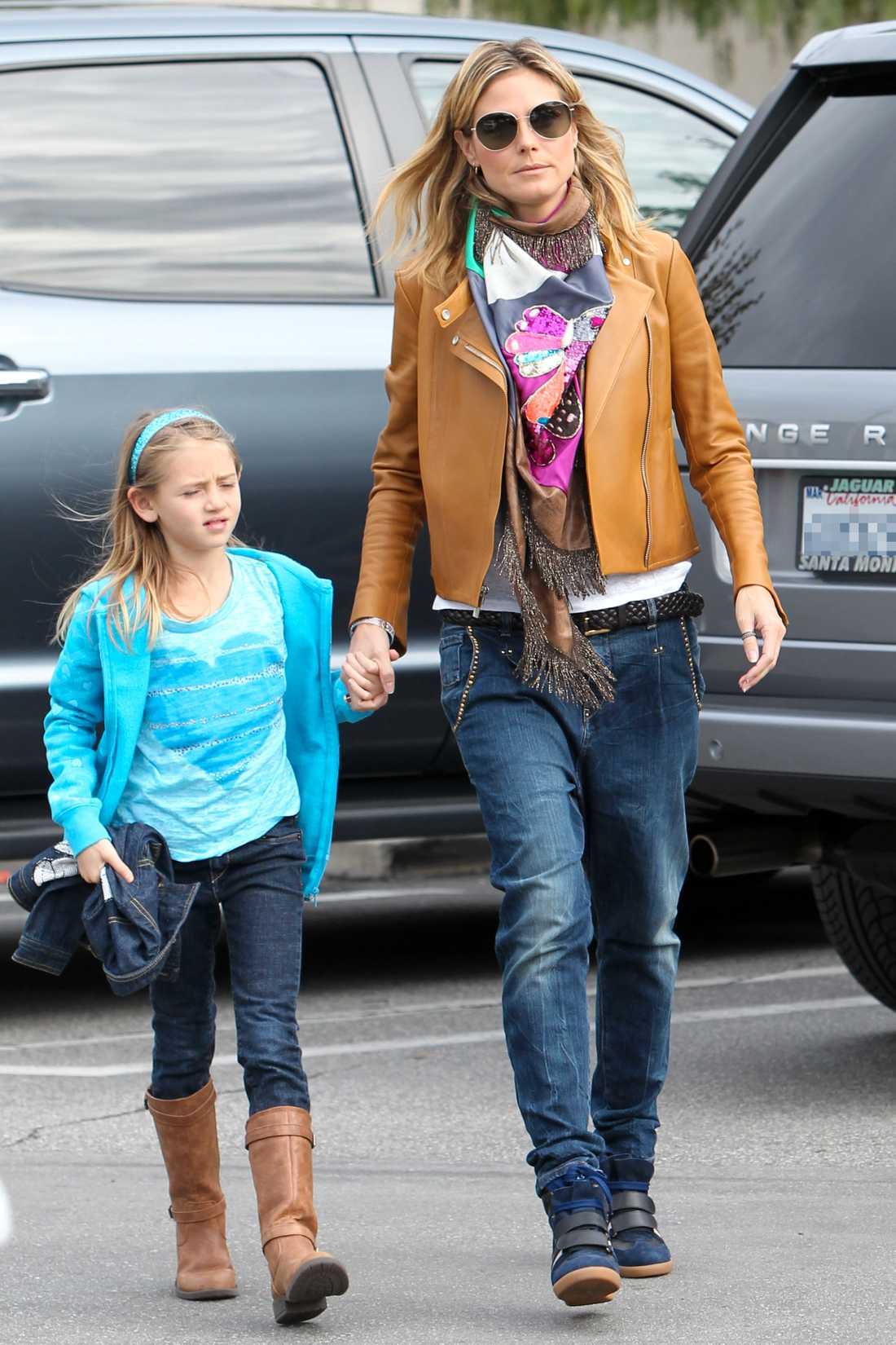Heidi Klum gör en avslappnad stil av lösa jeans, skinnjacka, stor sjal och sneakers.