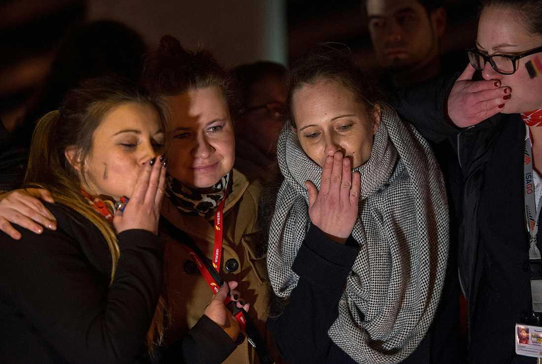 Flygplatsanställda hedrar offren för terroratackerna vid en ceremoni nära flygplatsen Zeventem på onsdagskvällen.