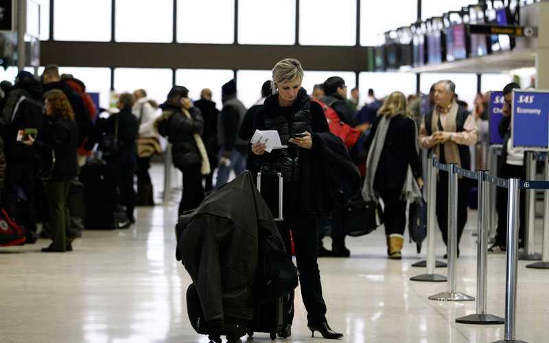 En resenär kollar sin mobil på Newark Liberty International Airport. Personalen jobbar febrilt med att boka om oräkneliga strandade passagerare efter att snökaoset slagit till mot USA.