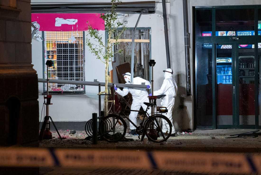 Polisens kriminaltekniker undersöker området kring livsmedelbutikens entré.