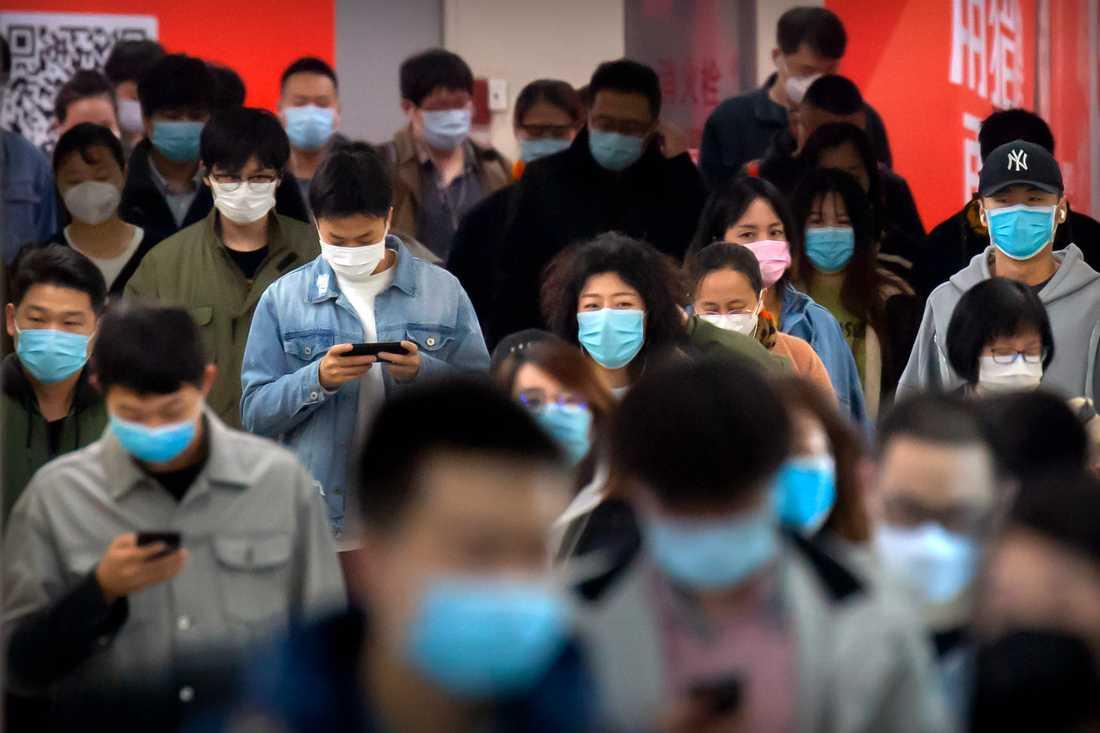 Resenärer med munskydd i Pekings tunnelbana.