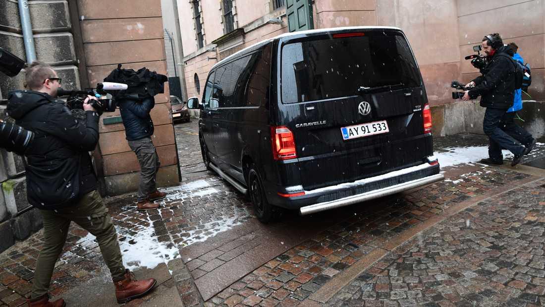 En svart polisbil anländer till rätten strax innan rättegången mot Peter Madsen inleds.