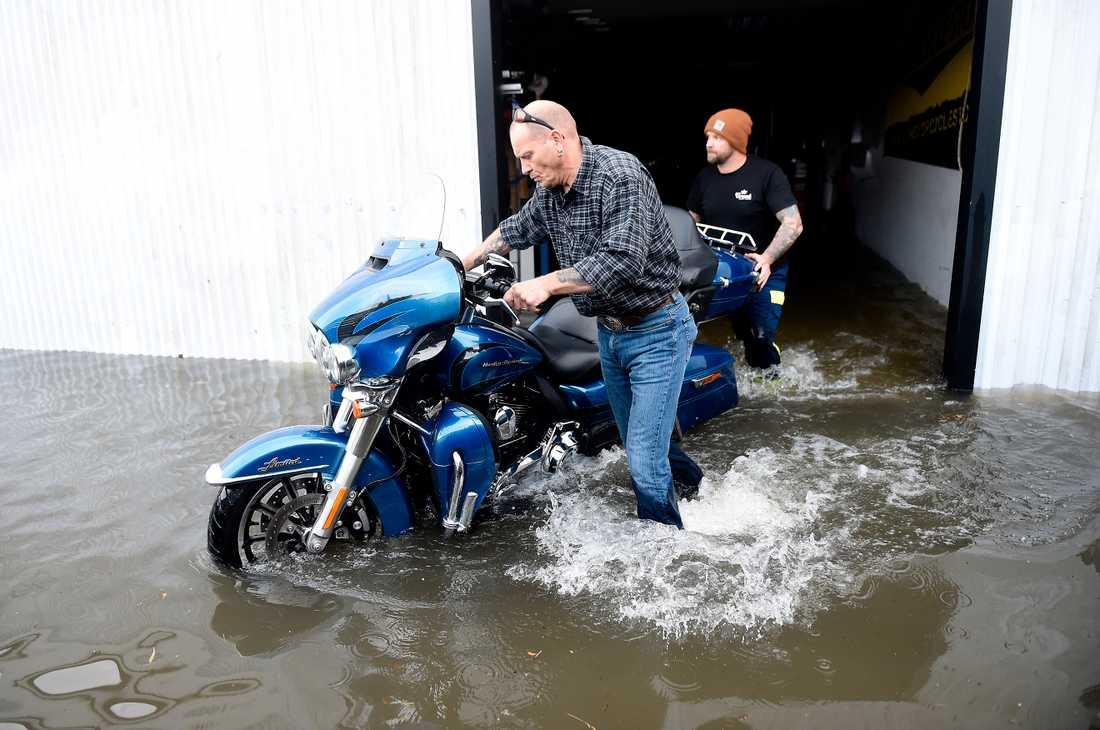 Motorcyklar räddas undan hos Custom By Kent utanför Bjuv efter att kraftiga åskskurar drabbat södra Sverige på onsdagen.