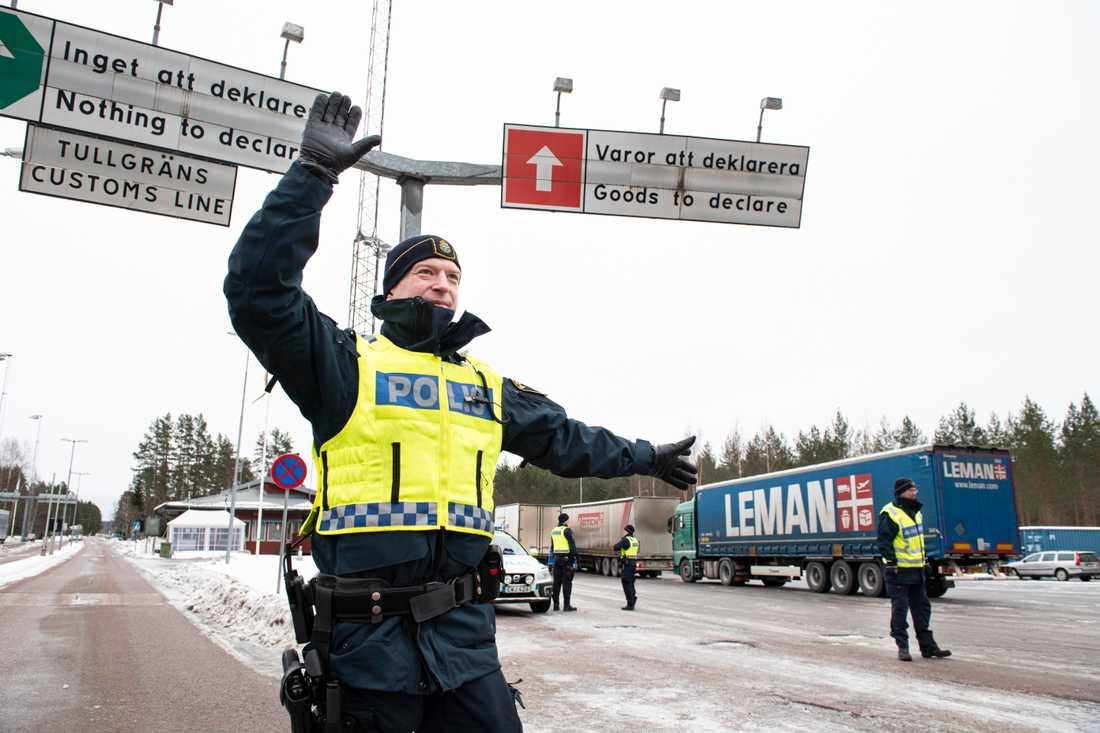 Andreas Berggren vinkar in bilarna som ska kontrolleras vid gränsen nära värmländska Charlottenberg.