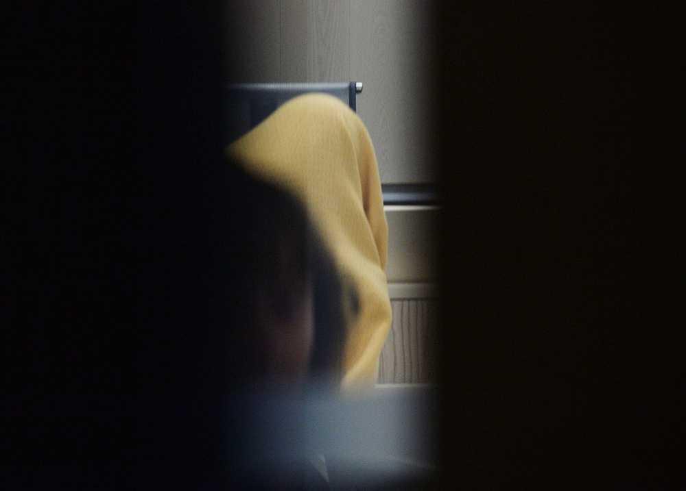 24-åriga kvinnan doldes under en gul handduk vid häktningsförhandlingen i Örebro tingsrätt.