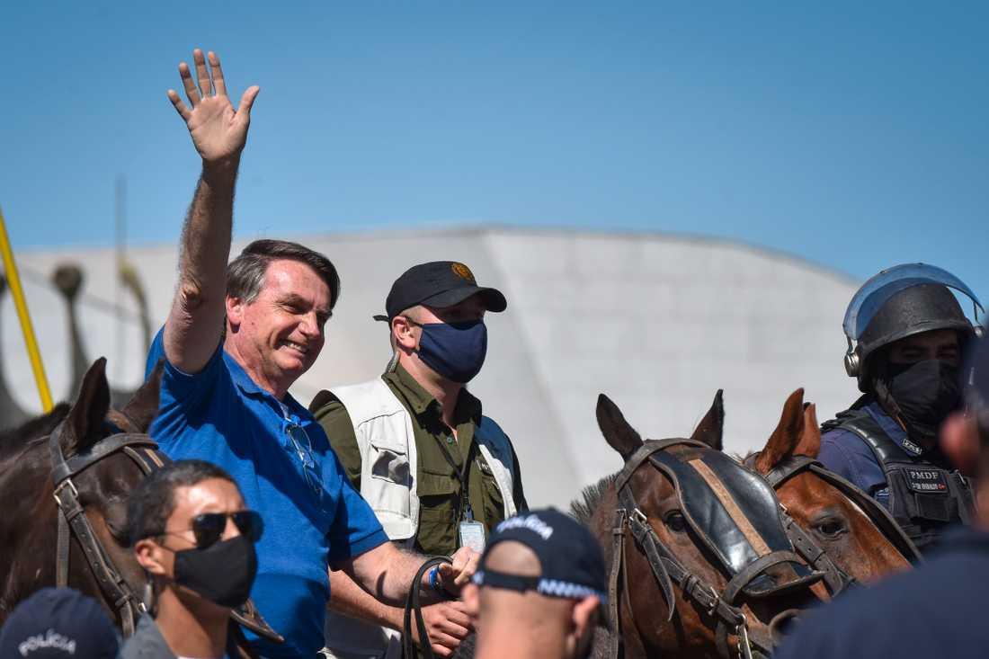 Brasiliens president Jair Bolsonaro till häst möter anhängare utanför presidentpalatset i huvudstaden Brasilia.