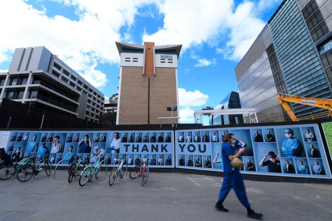 En man i mask utanför en vägg med hyllningar till vårdpersonalen i Melbourne, i delstaten Victoria.