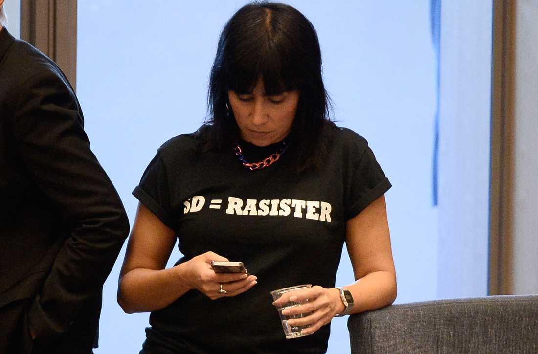 """Rossana Dinamarca (v) har tidigare protesterat i kammaren mot SD, bland annat genom att bära en t-shirt med texten """"SD=rasister""""."""