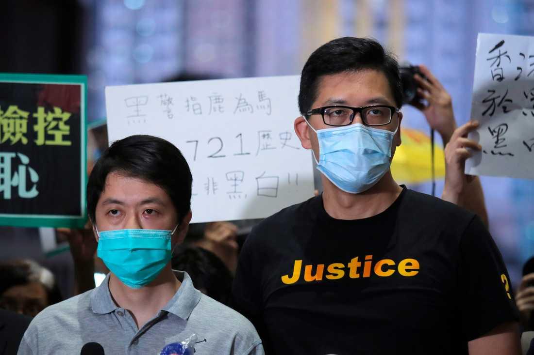 Demokratiförespråkarna Ted Hui (till vänster) och Lam Cheuk-Ting sedan de släppt mot borgen i Hongkong i augusti. De misstänks för brott med anknytning till regimkritisk verksamhet. Arkivbild.