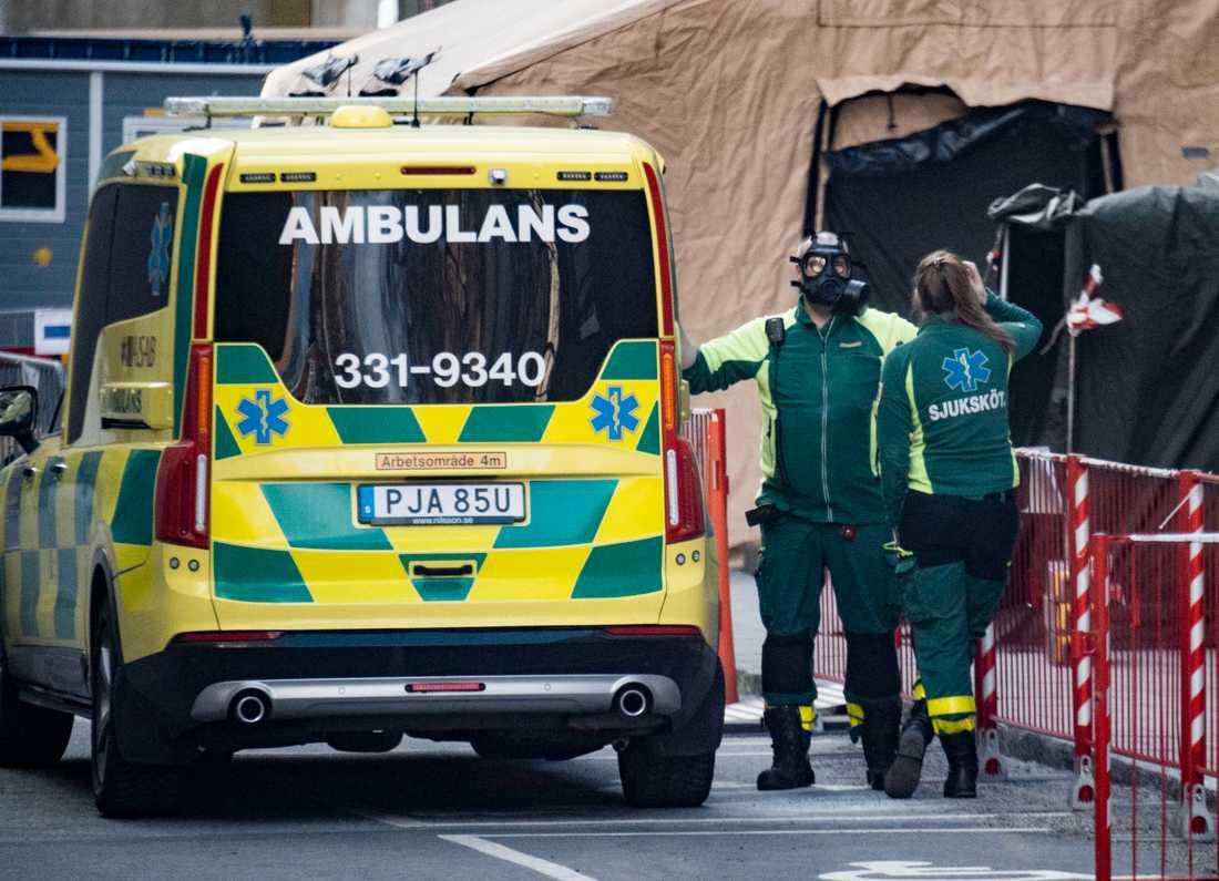 Ambulanssjukvårdare med skyddsmask tar hand om misstänkt coronasmittad.