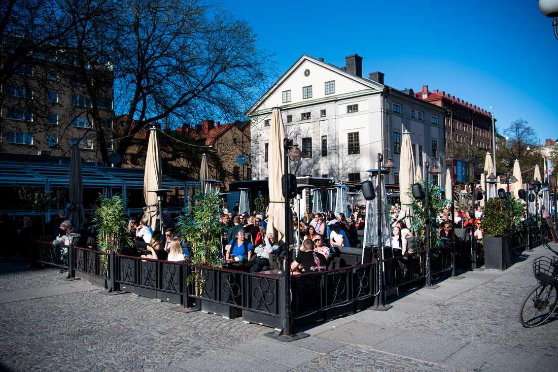 Folk sitter på uteserveringar på Medborgarplatsen i Stockholm trots covid-19-pandemin. Arkivbild.