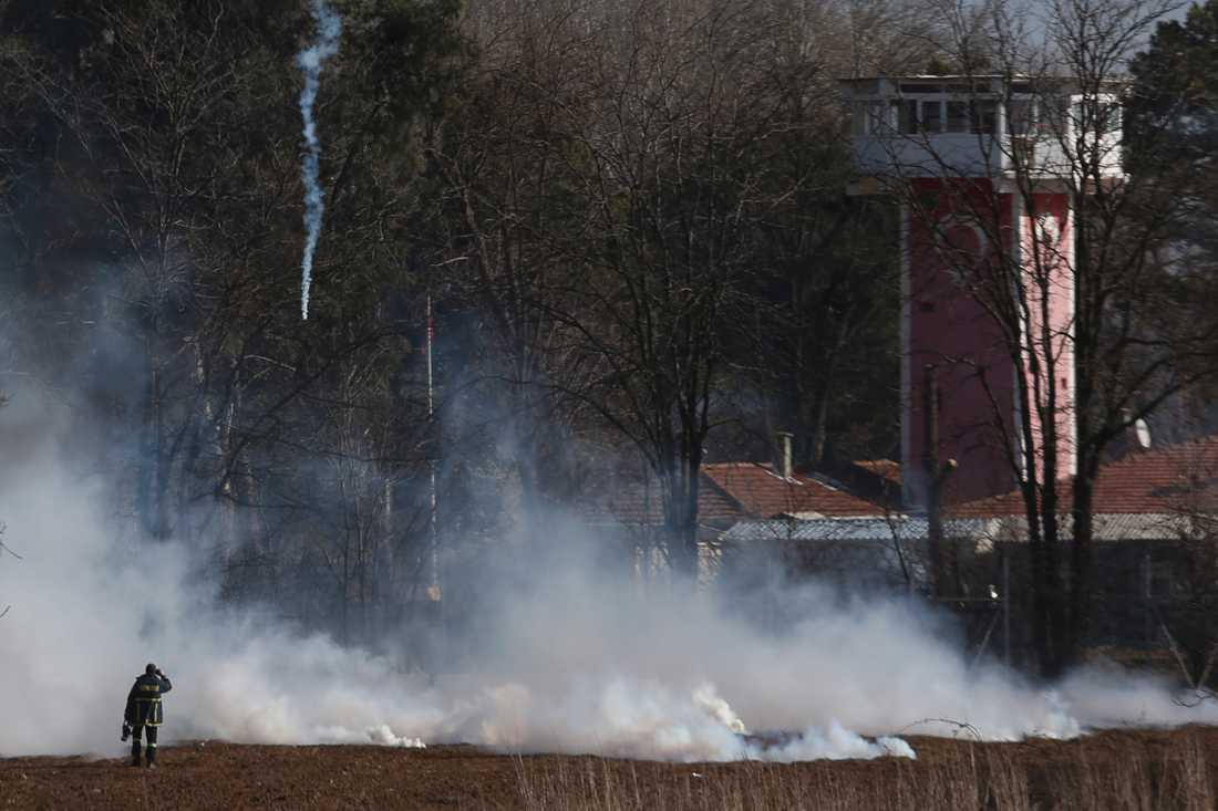 En grekisk brandman nära gränsstängslet medan tårgas används under oroligheterna vid gränsen mellan Grekland och Turkiet.