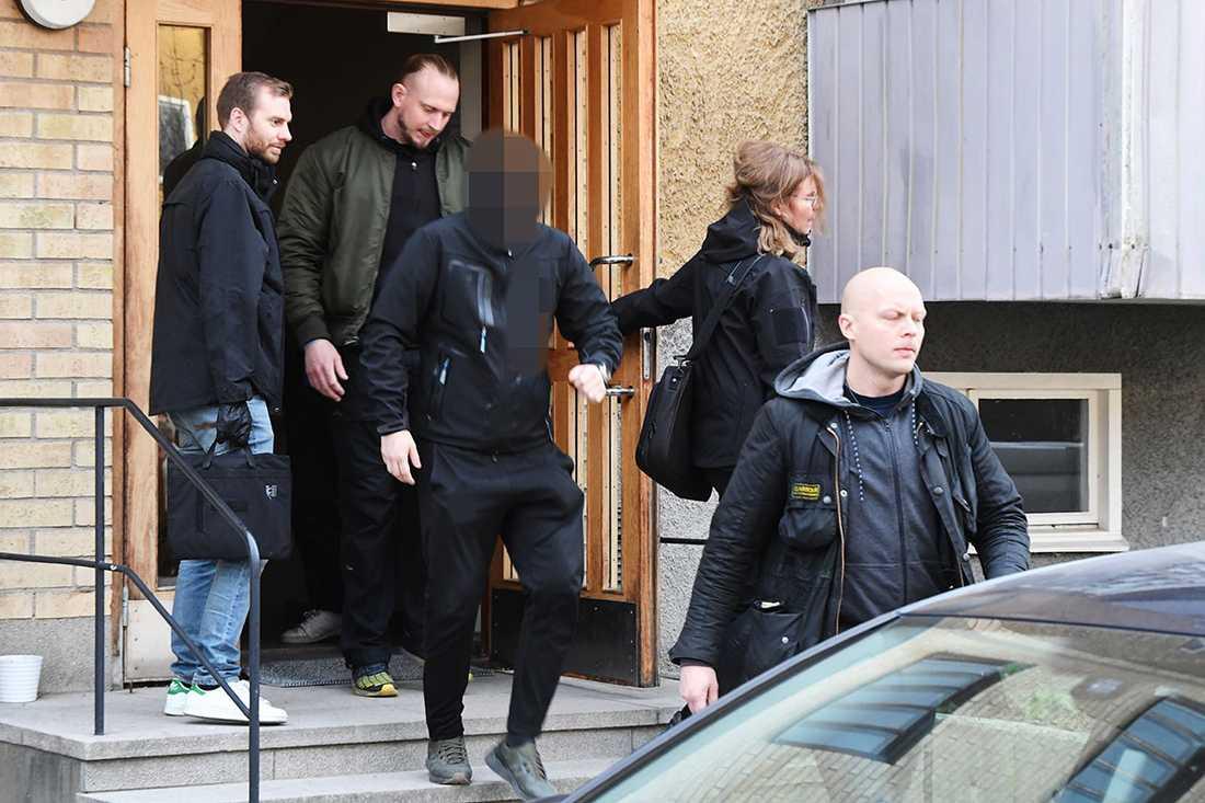 En man förs ut från lägenheten i Vårberg.